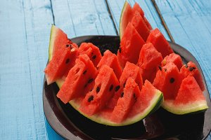 Fresh slices of watermelon on a blue