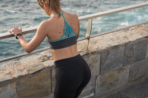 A sporty woman looks down at the sea