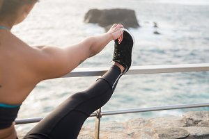 Woman by the sea with leg on railing