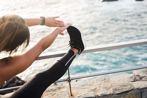 A woman doing stretches by the sea s