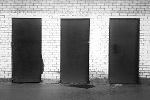 Three black and white closed doors b