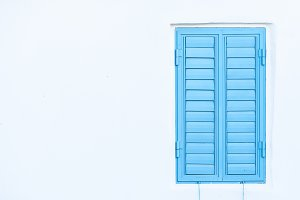 Blue window shutters on a white wall