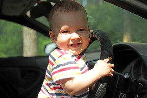 Little boy smiling holding the wheel