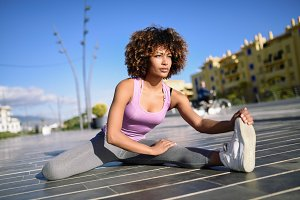 Young black woman doing stretching a