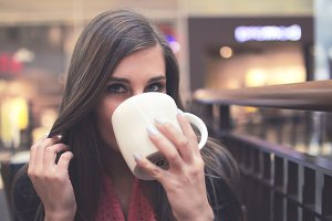 A young girl drinking coffee