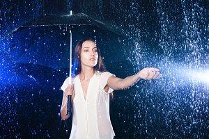 Young woman under umbrella.