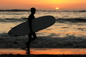 surfer silhouette in beach at sunset
