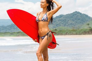 Sporty girl with red surf on the bea
