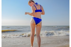 Woman in a blue swimsuit by the sea