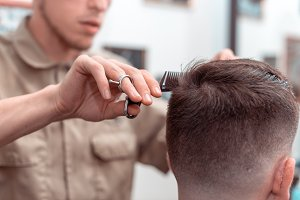 Barber in Barbershop shear hair