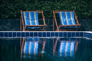 Two Blue Beach Chairs by Pool
