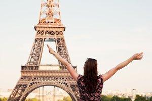 Happy woman against Eiffel Tower