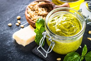 Pesto sauce with ingredients on dark