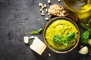 Pesto sauce with ingredients on dark