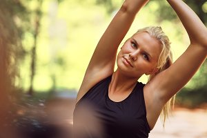 Fit young woman stretching before a