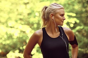 Sporty young woman listening to musi