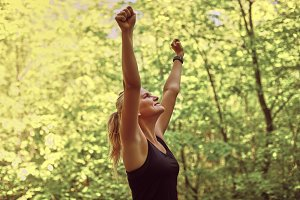 Woman raising her arms in triumph af