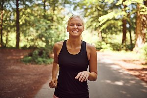 Smiling young blonde woman jogging a
