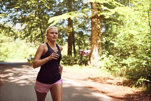 Fit young blonde woman jogging alone