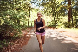 Fit young woman jogging alone throug