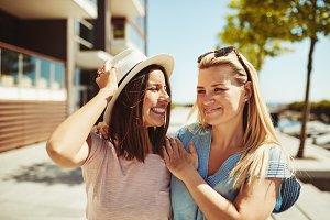 Two laughing young girlfriends walki