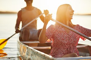 Young woman laughing while canoeing