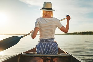 Young woman canoeing on a still lake