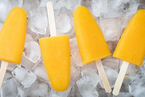 Orange popsicles with juice on a ice