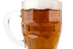 Beer with foam in a glass on a white