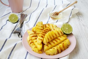 Grilled pineapple wedges on pink