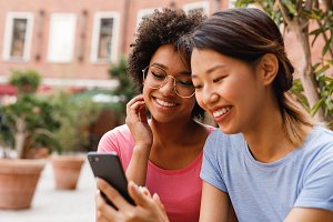 Two smiling women looking at phone
