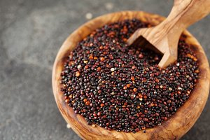 Seeds of black quinoa in wooden bowl