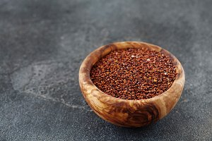 Seeds of red quinoa in wooden bow co
