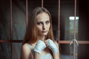 Young woman fighter stands in a figh