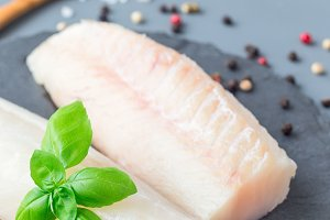 Fresh raw cod fillet with spices, pe