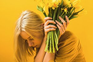 girl holding beautiful yellow tulips