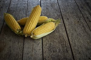Fresh sweet corn on wooden table