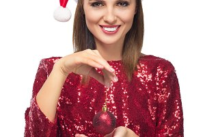 girl in santa hat holding bauble