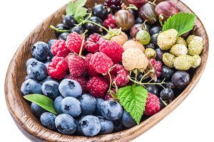 Berries in the wooden bowl on a whit