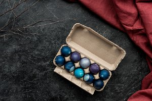 Painted eggs in egg carton on dark b