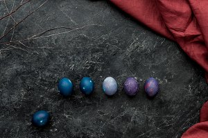 Row of colored eggs on dark backgrou