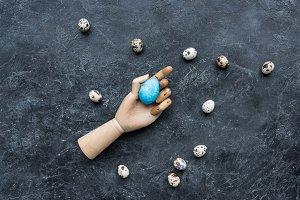 Quail eggs around mannequin hand wit
