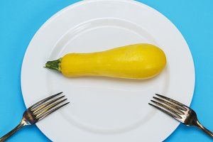 raw yellow squash in a white plate