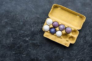 Egg carton with Easter eggs on dark