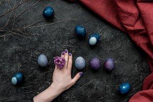 Female hand by Easter eggs on dark b
