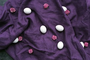 White eggs and flowers on textile ba