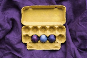 Three Easter eggs in carton on texti