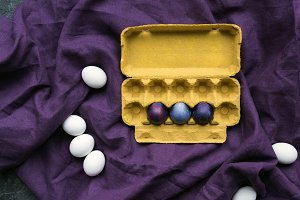Colored eggs in egg carton and white