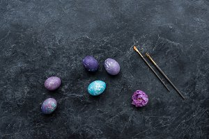 Painted eggs with brushes on dark ba