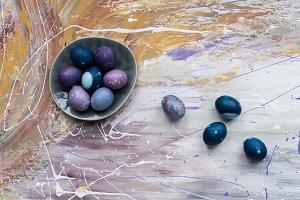 Easter eggs in bowl and on stained b